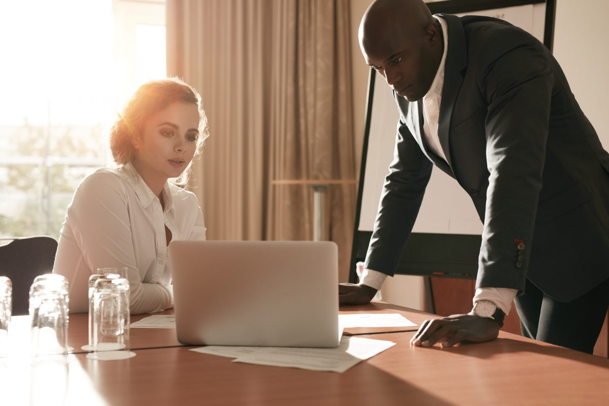 Two business people looking at business plan on laptop. Businessman and businesswoman in conference room working on business strategy.