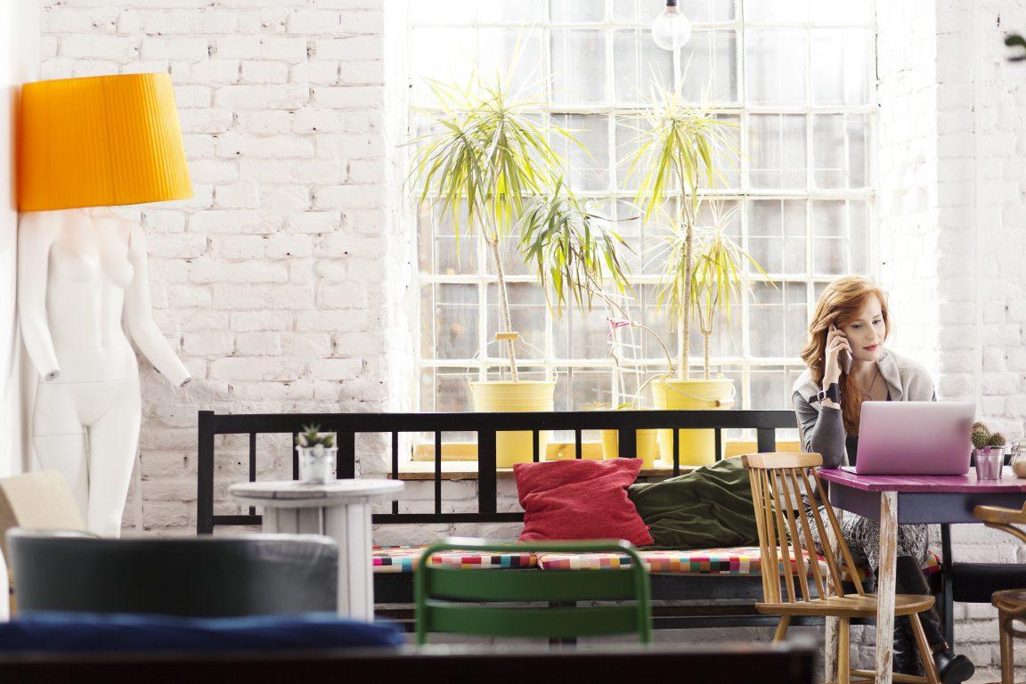 Copywriter woman using notebook and smartphone working in loft studio