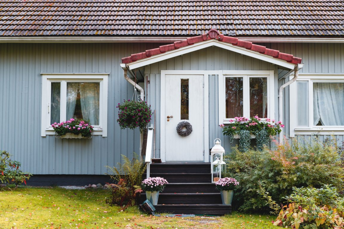 Fragment of wooden finnish blue house with decorated entrance. Rural scene, country lifestyle.