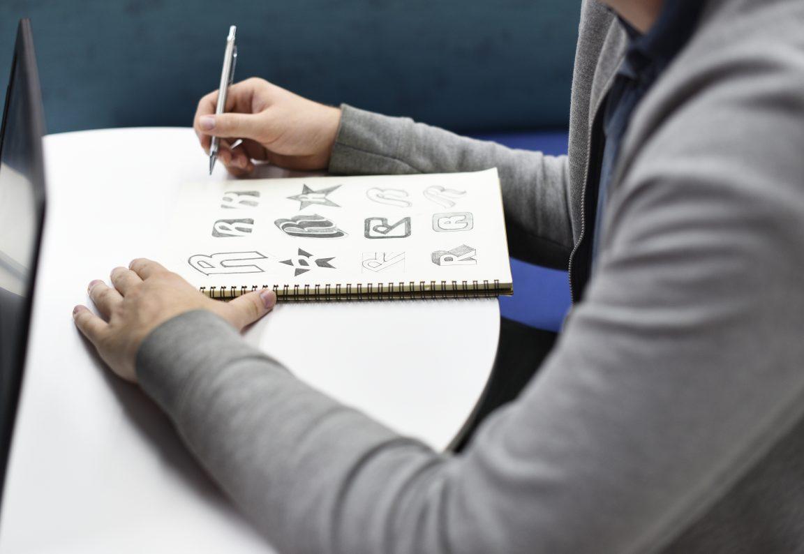 hand holding notebook with drew brand logo creativ P8HTW8W