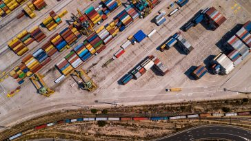 Industrial Cargo area with container ship in dock at port, Aerial view of transport pier.