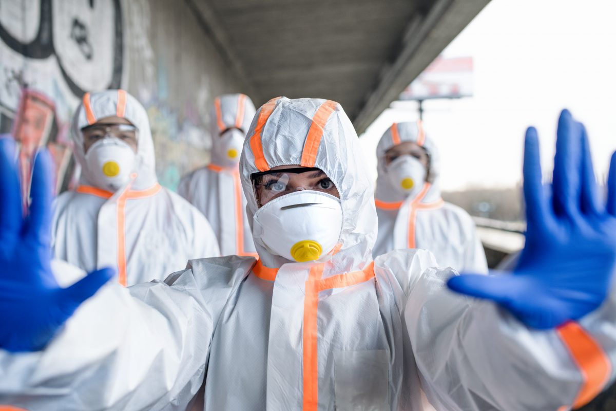 People with protective suits and mask respirators outdoors, coronavirus concept.