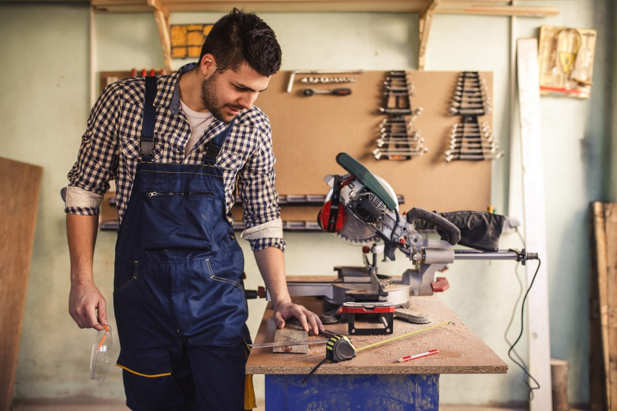 Portrait of a young handsome carpenter working in workshop.