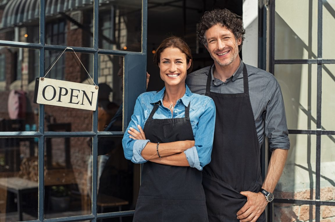 Two cheerful small business owners smiling and looking at camera while standing at entrance door. Happy mature man and mid woman at entrance of newly opened restaurant with open sign board. Smiling couple welcoming customers to small business shop