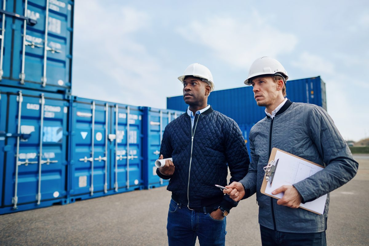 Two engineers wearing hardhats and discussing logistics together while standing in a freight yard full of shipping containers