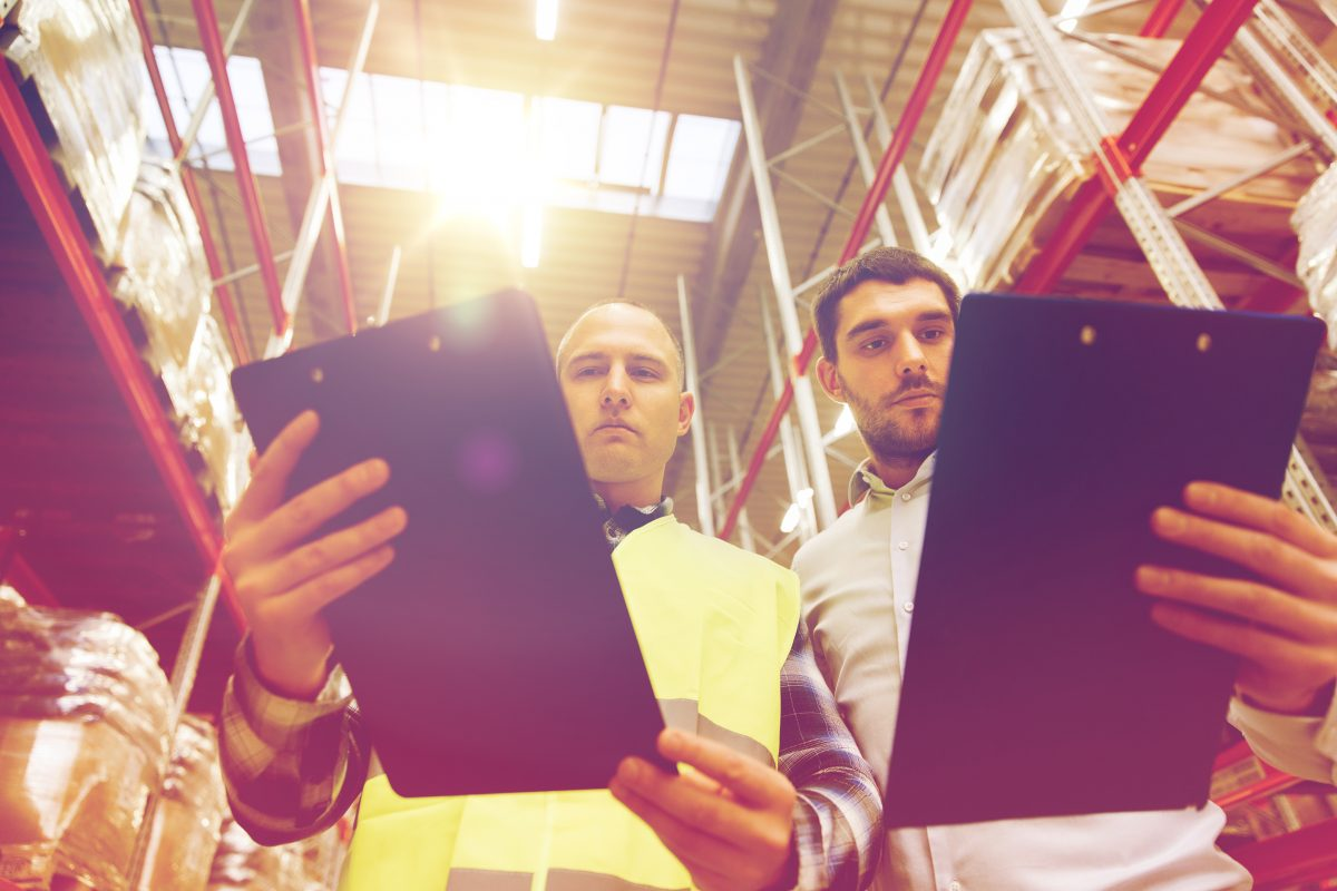 wholesale, logistic, people and export concept - manual worker and businessmen with clipboards at a warehouse