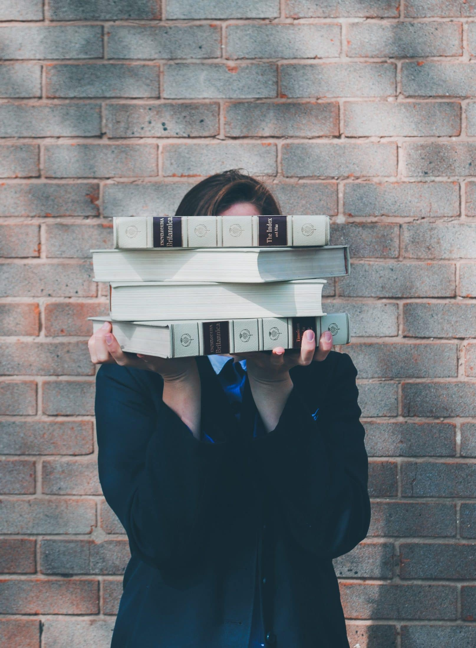 person holding pile of books near face