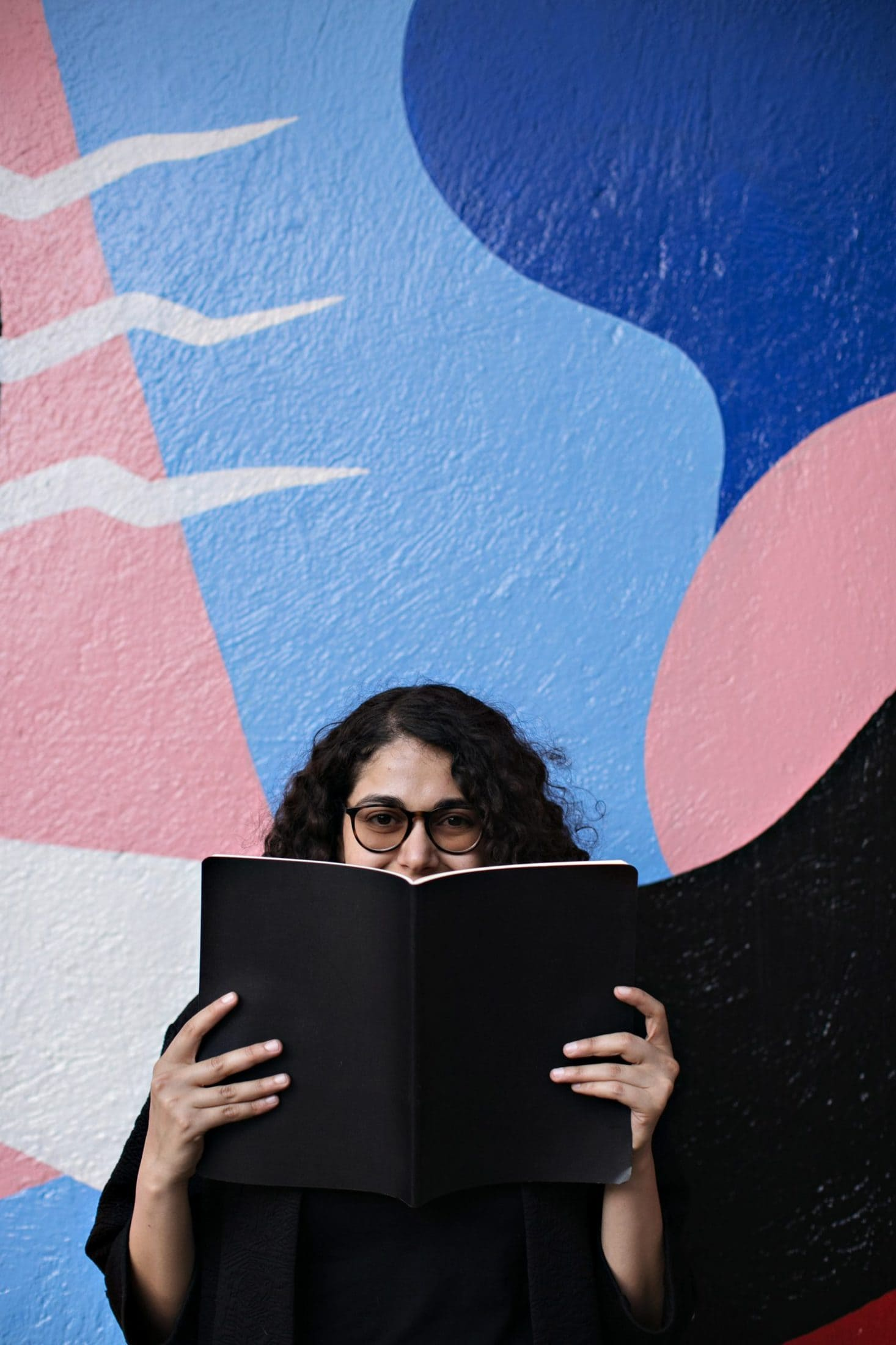 woman standing and holding open book covering her mouth