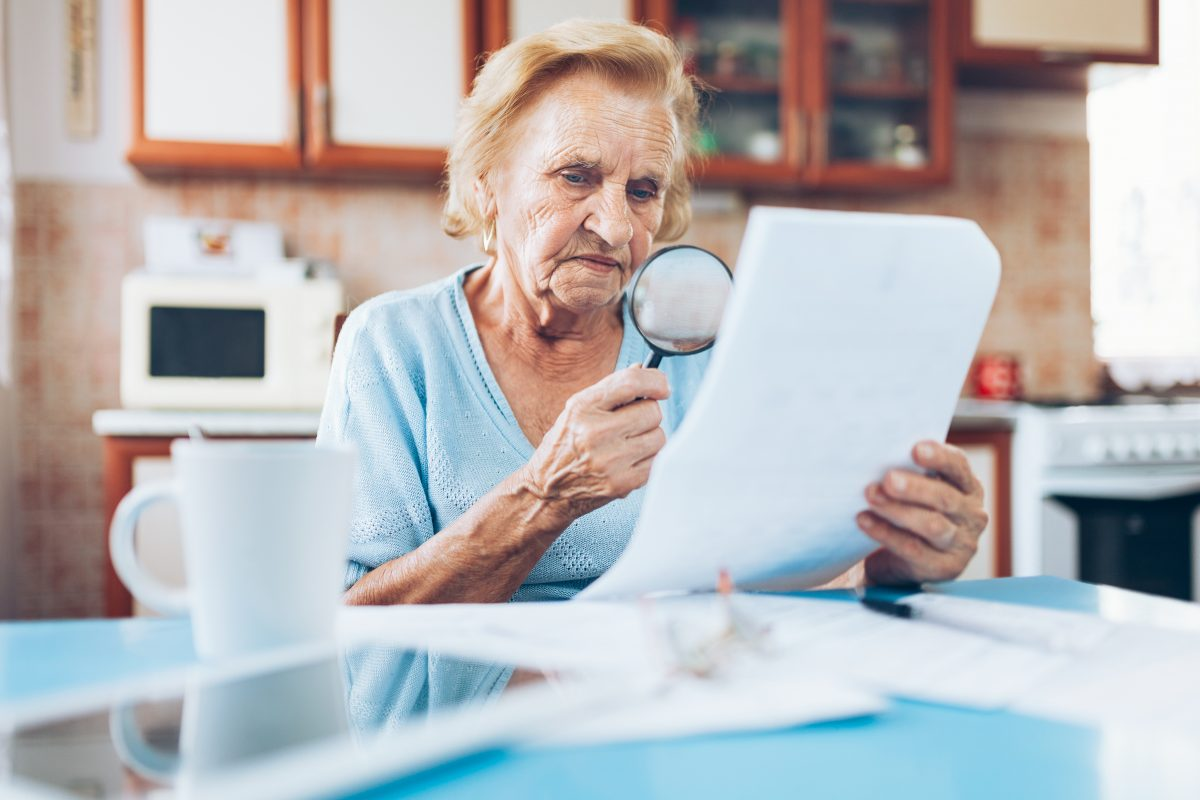 elderly woman looking at her utility bills 67AYR2L