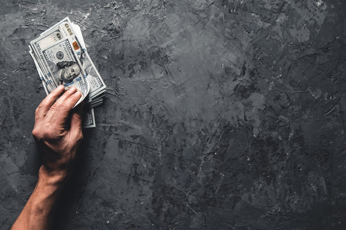 hand holding money against dark background busines 7XPLFM9