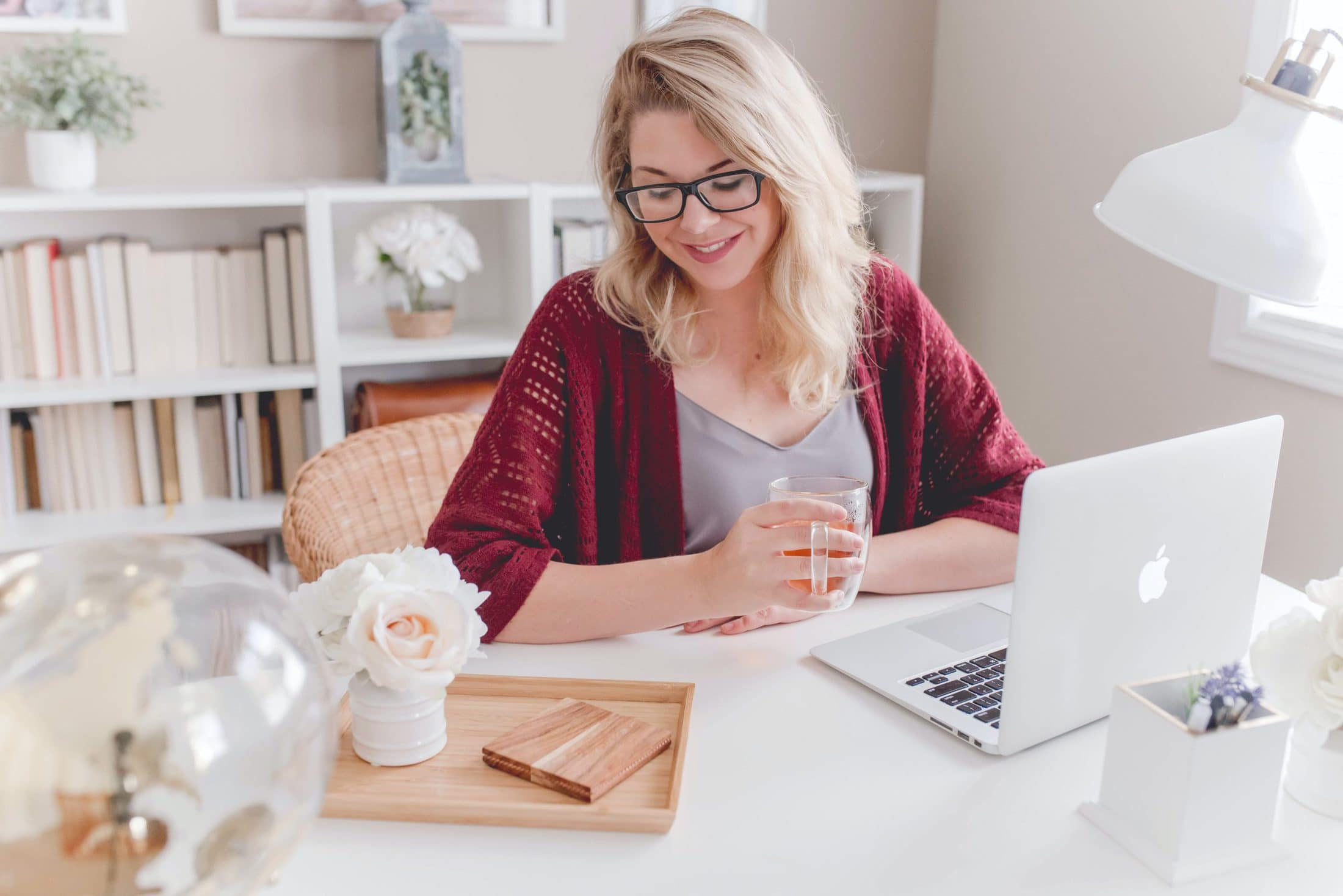 woman smiling holding glass mug sitting beside table with MacBook