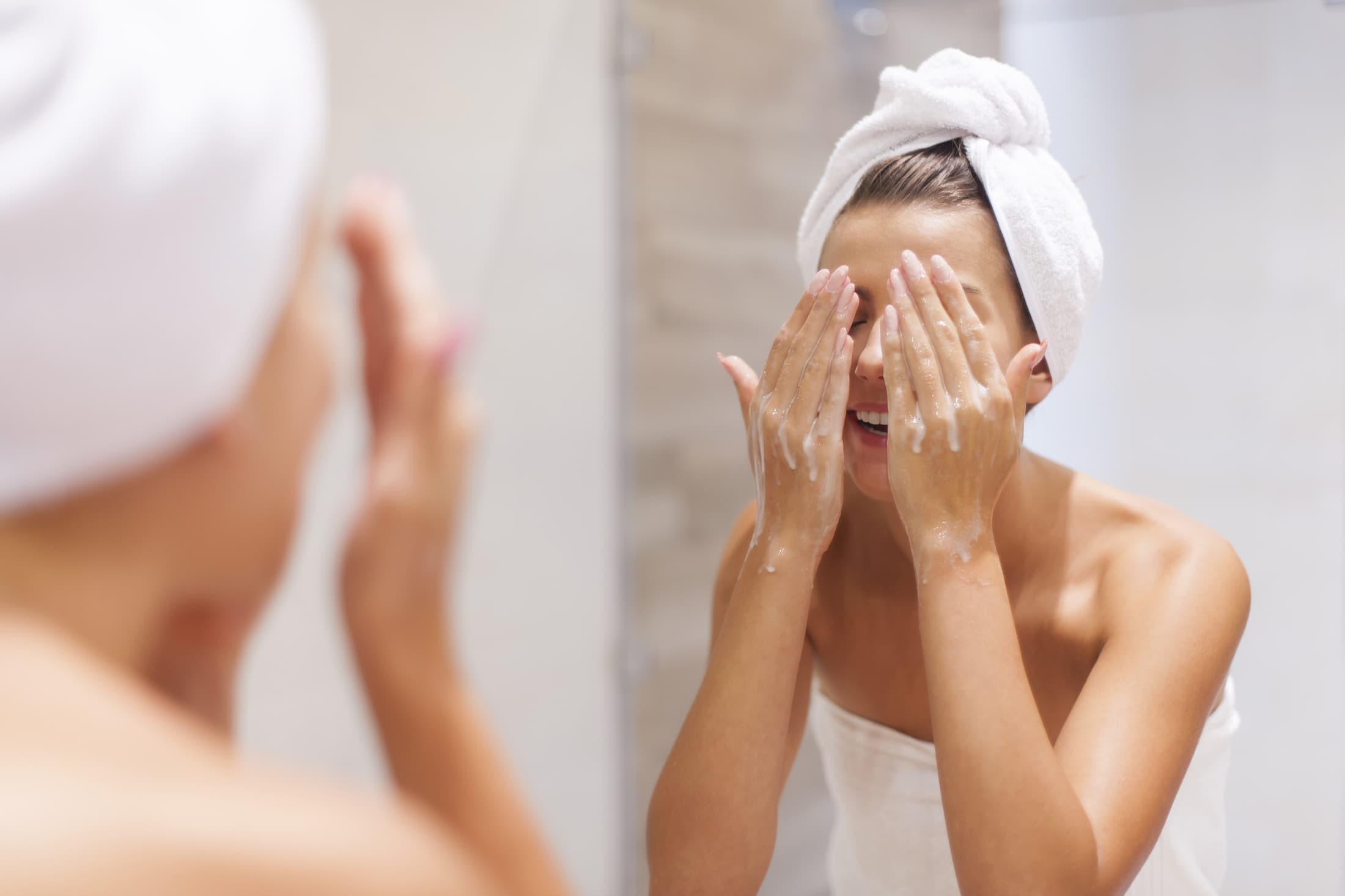 woman washing face in bathroom CKM4N2Z