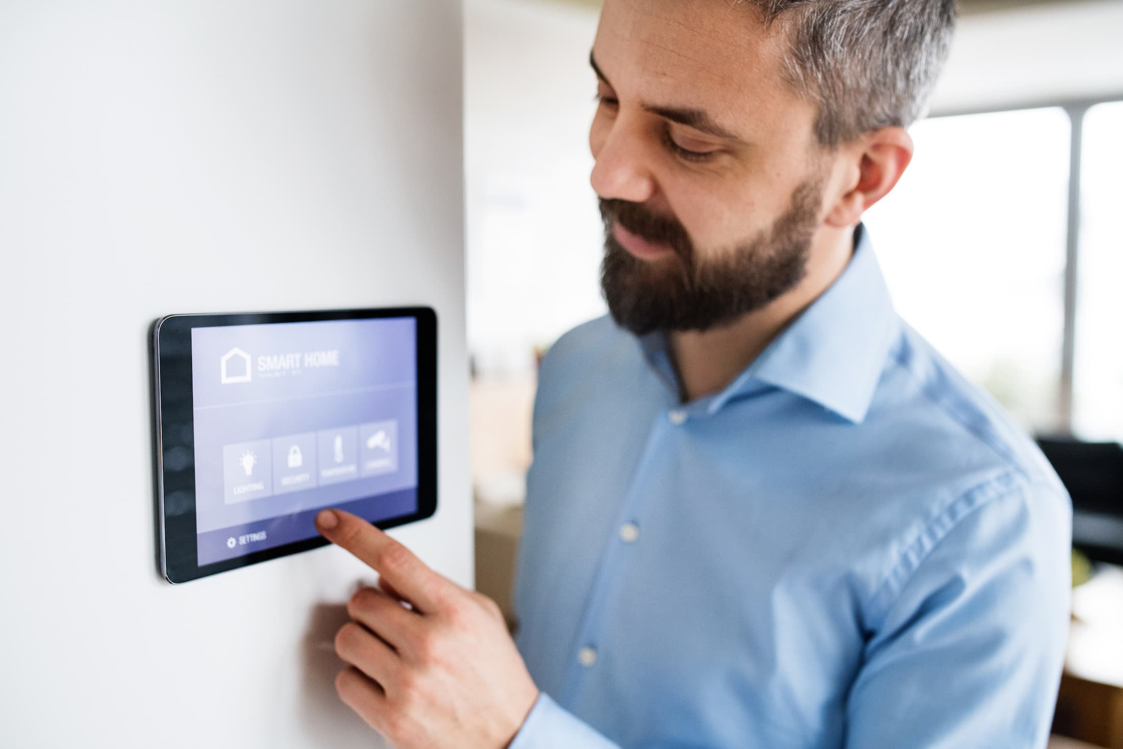 a man pointing to a tablet with smart home screen PM4HLYX