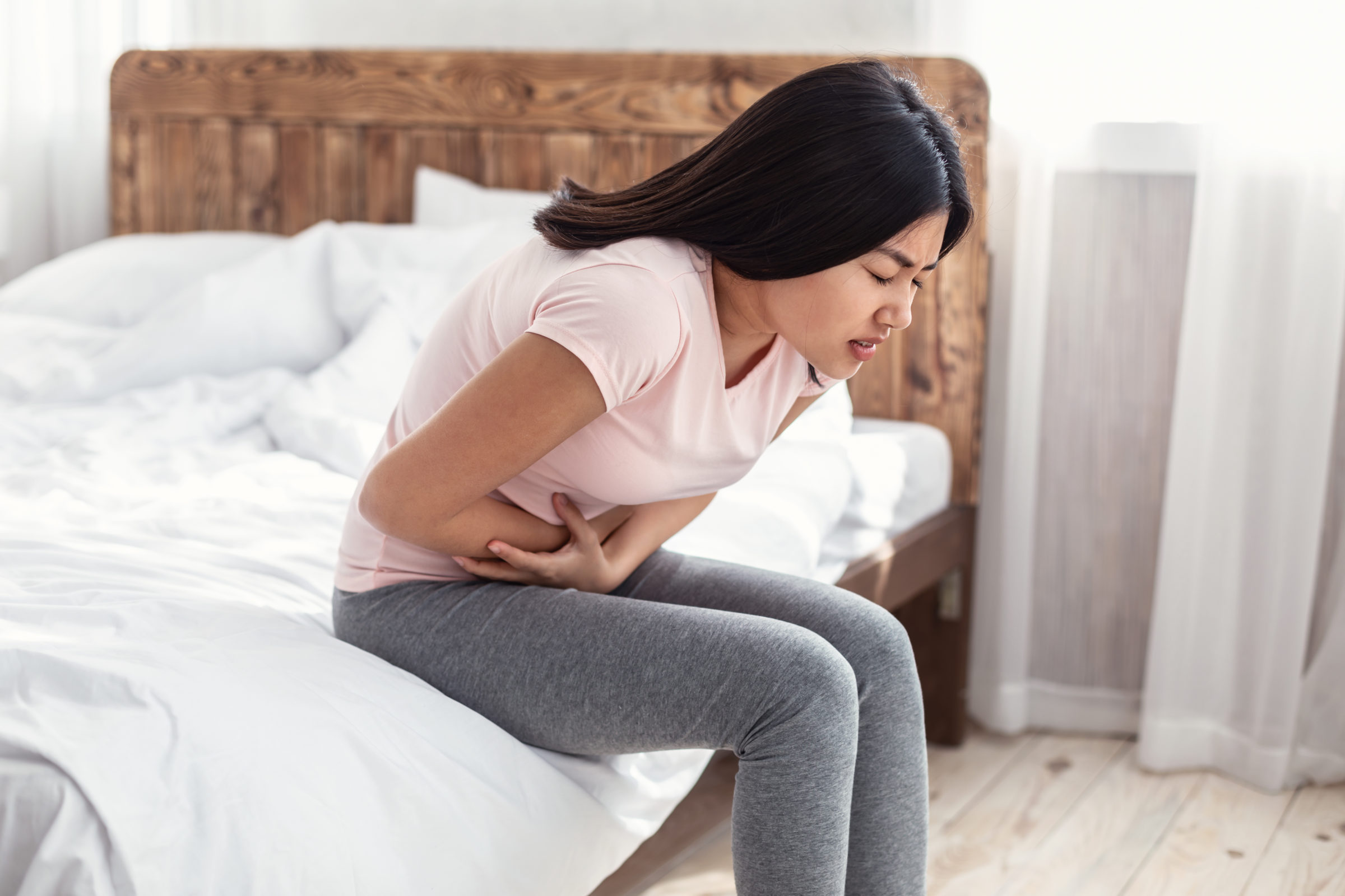 asian woman having stomachache suffering from pain G2MFNZB