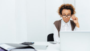Concentrated african american young woman accountant in glasses working in office using laptop
