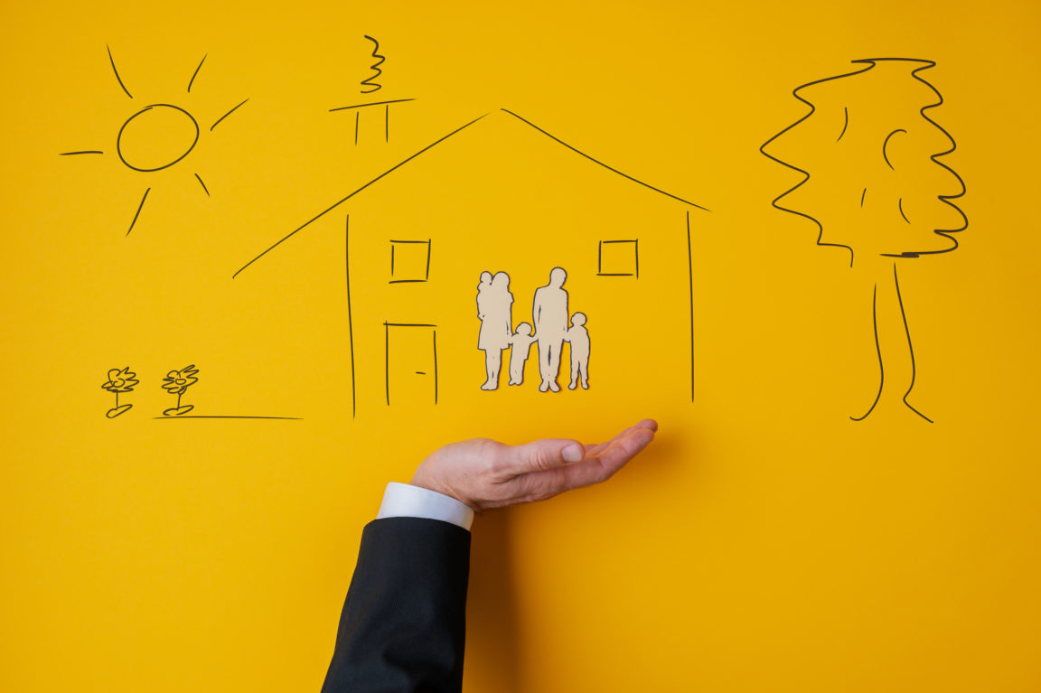 Male hand in a suit in supportive gesture under a hand drawn house with a paper cut silhouette of a family inside in conceptual image. Over yellow background.