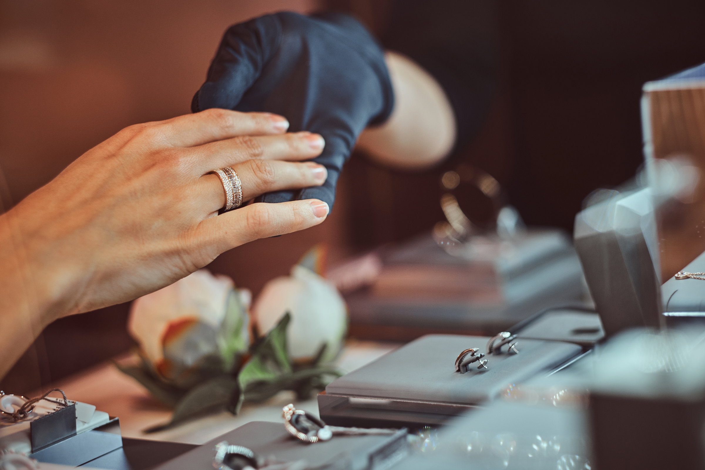 girl tries on wedding ring in luxury jewelry store D78JNSC