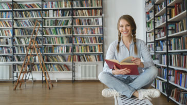 Smiling woman with a book in library