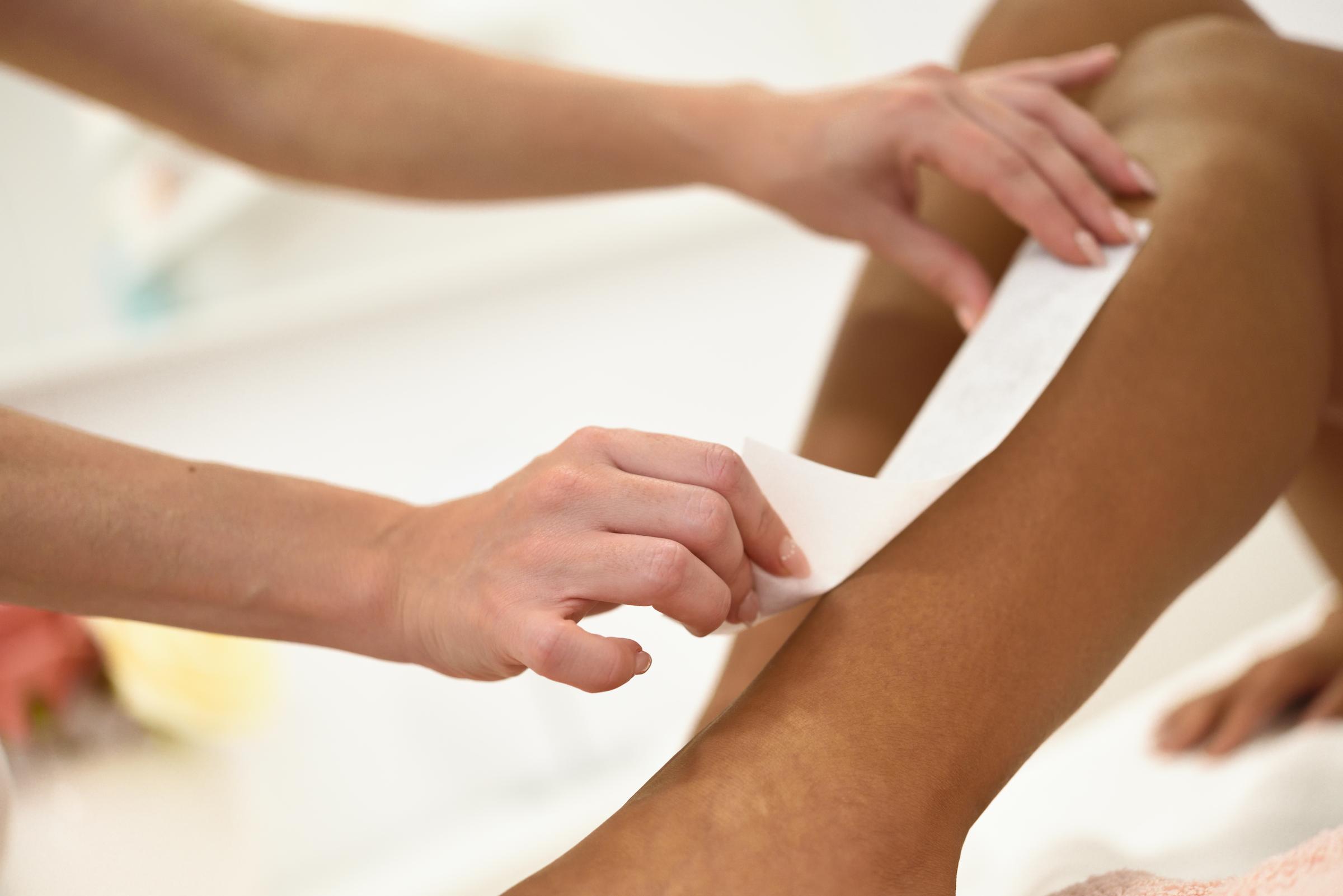 woman having hair removal procedure on leg applyin FX2MYTZ