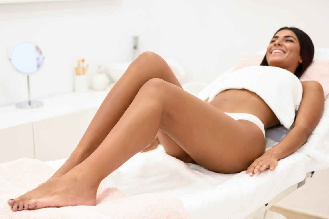Woman having hair removal procedure on leg applying wax strip depilatory in salon. Depilation concept