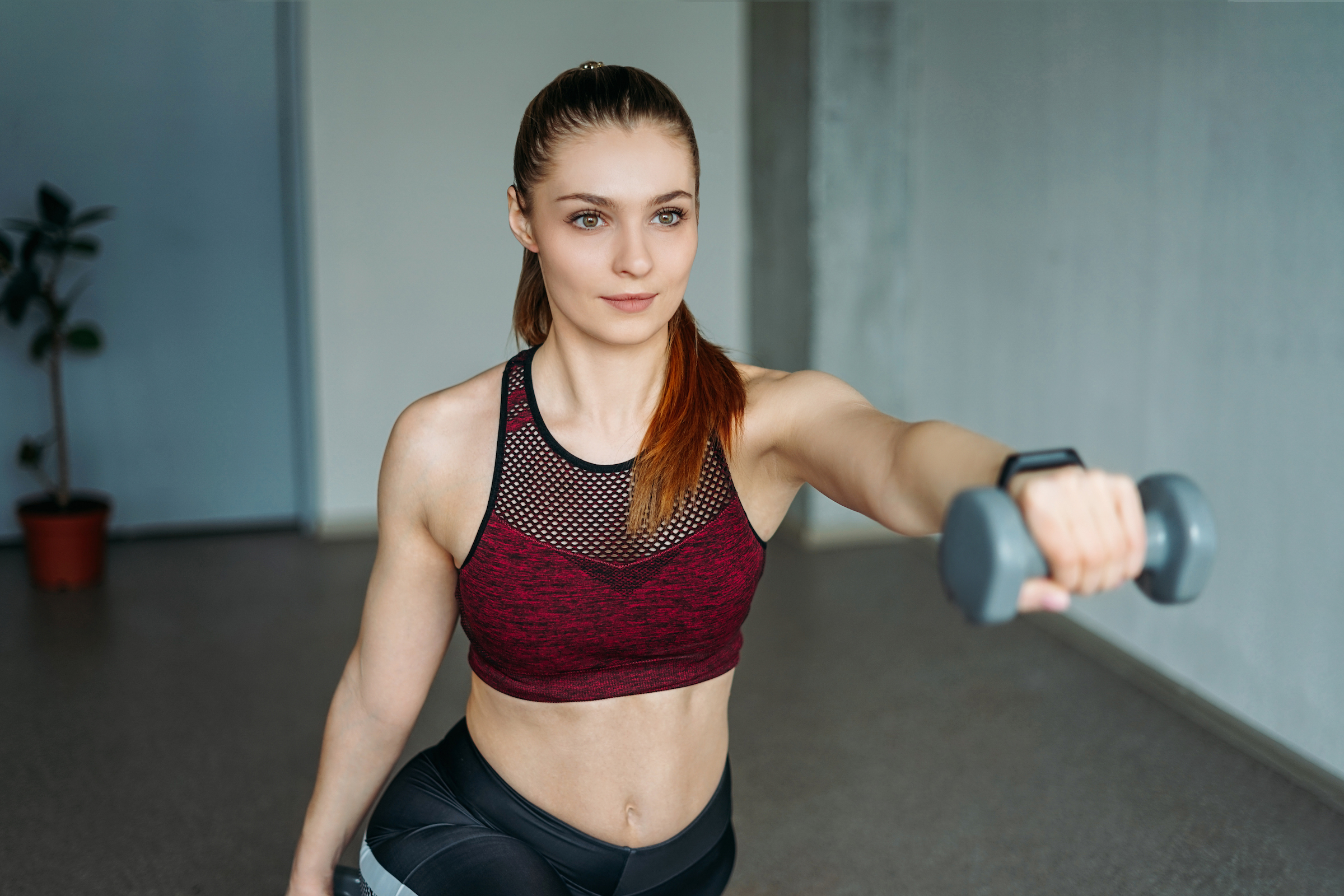 young woman in sport wear smiling girl trains with 5P3EX46