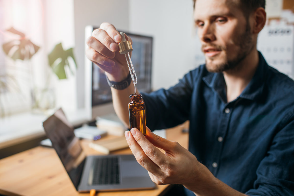 Vitamins and supplements. Hand holding pipette of Hemp oil. Close up man uses CBD oil. Medical cannabis. Healthy lifestyle