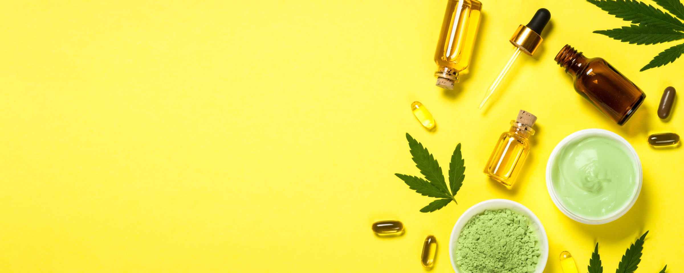 cannabis oil and green leaves at yellow table CH2WS8H