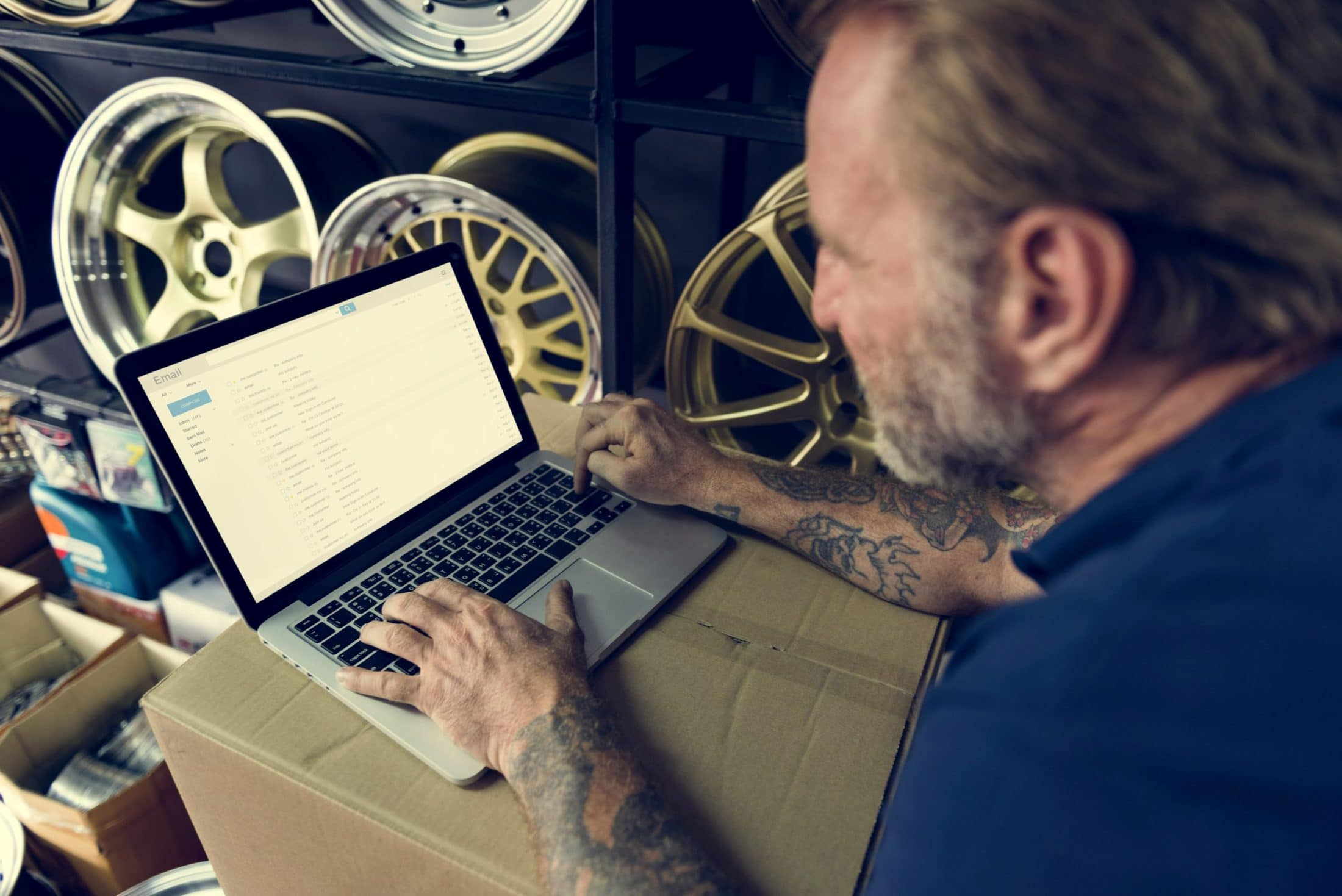 car parts shop owner warehouse checking emails con PJSTF33 scaled