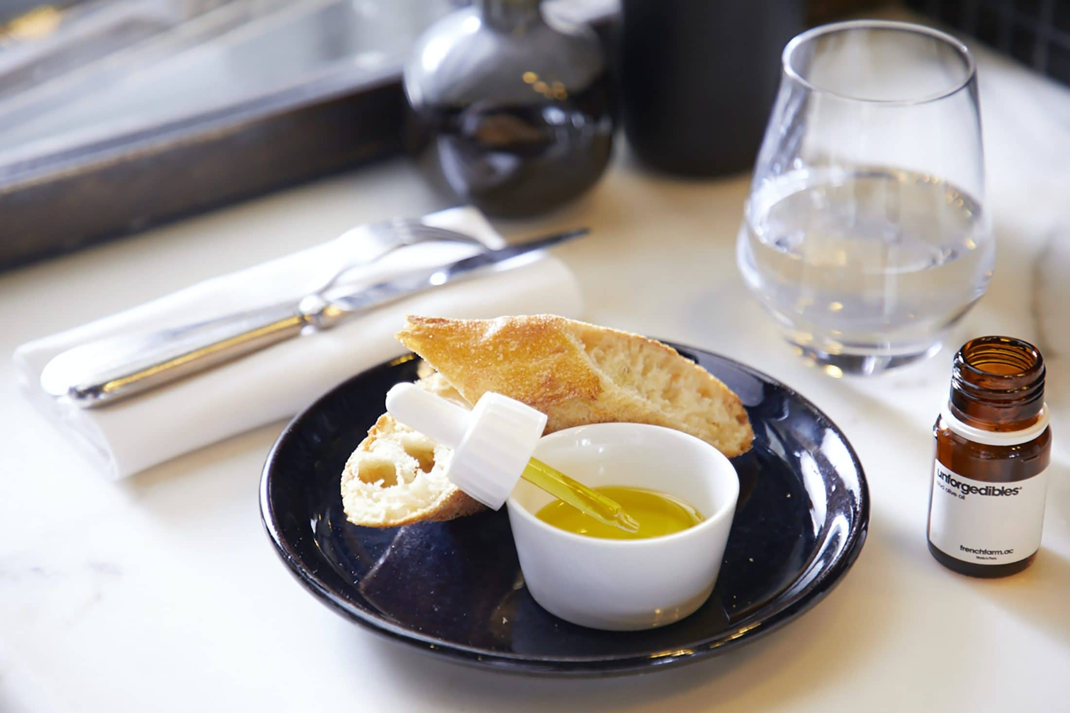 bread on black ceramic plate beside clear drinking glass