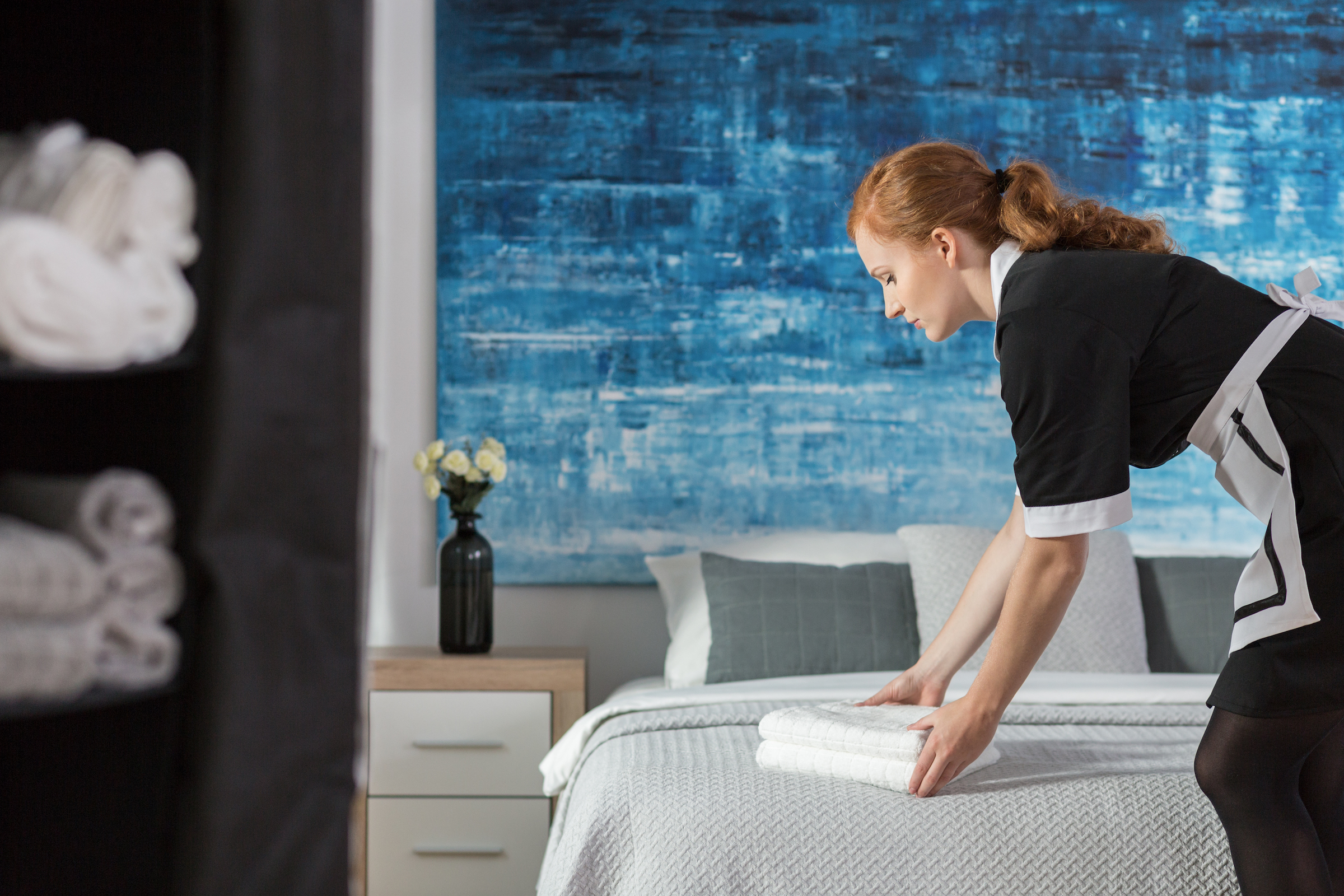 maid laying towels on bed P8DXHAB