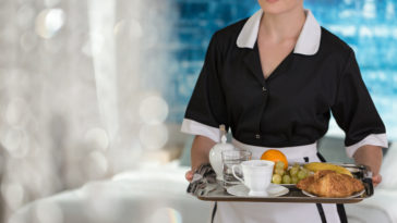 Maid holding a tray with fruit, coffee, water and croissants for a hotel guest