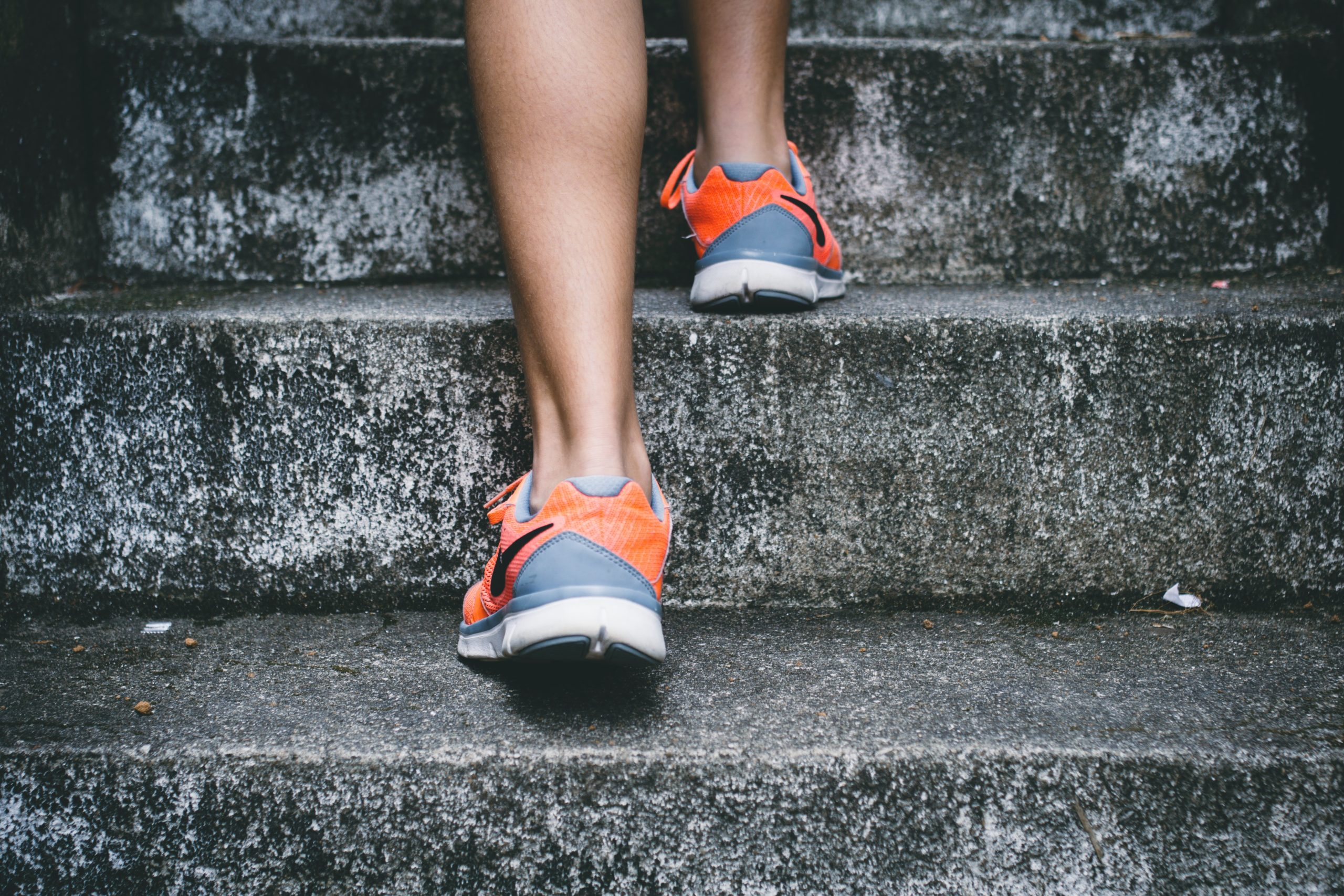 person wearing orange and gray Nike shoes walking on gray concrete stairs
