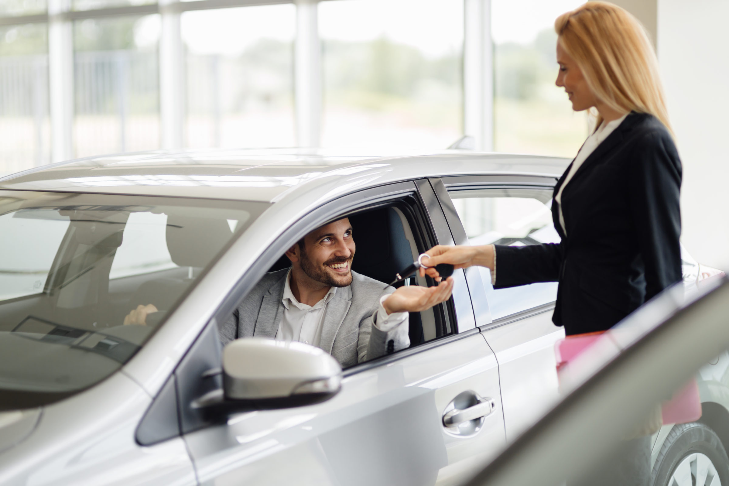 salesperson selling cars at dealership A94MRES