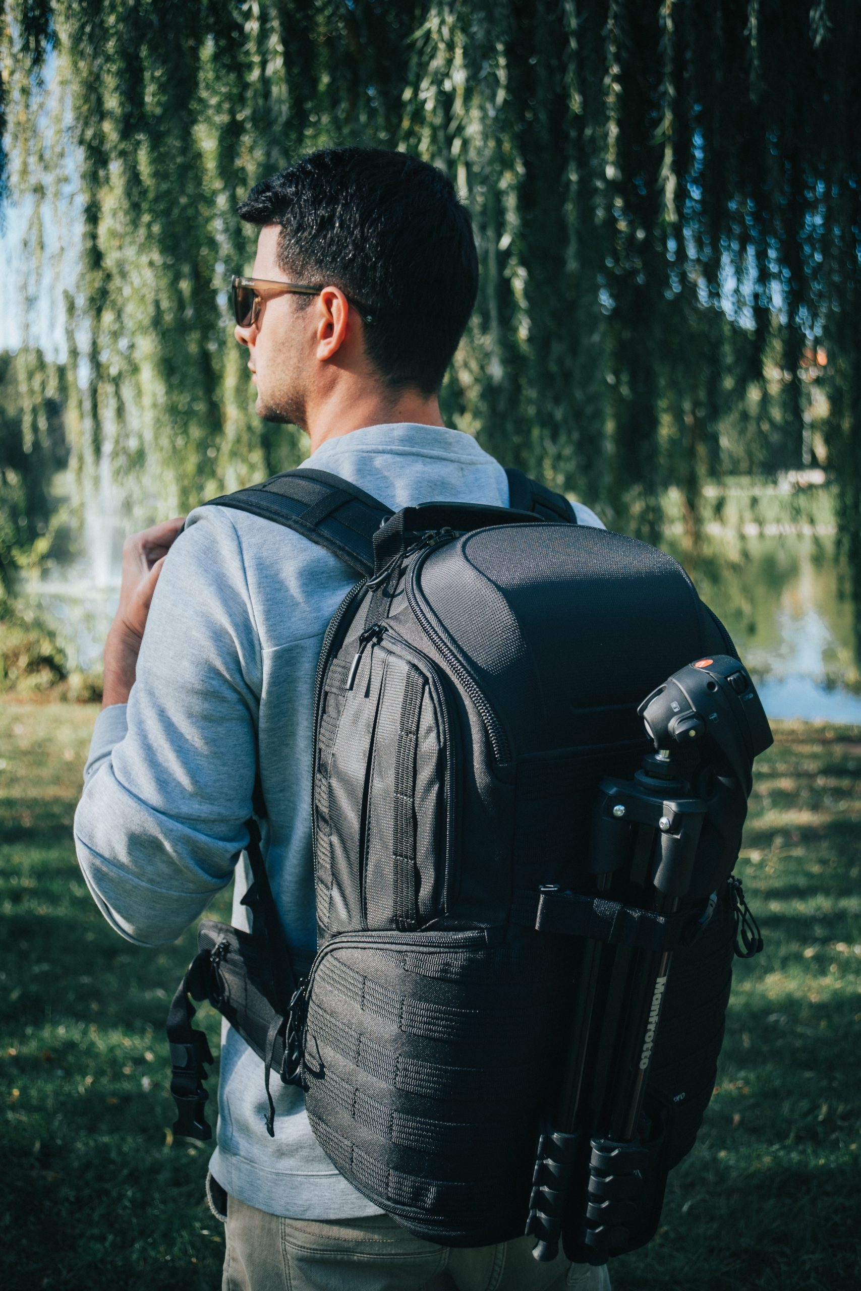 selective focus photography of man carrying backpack while standing near outdoor during daytime