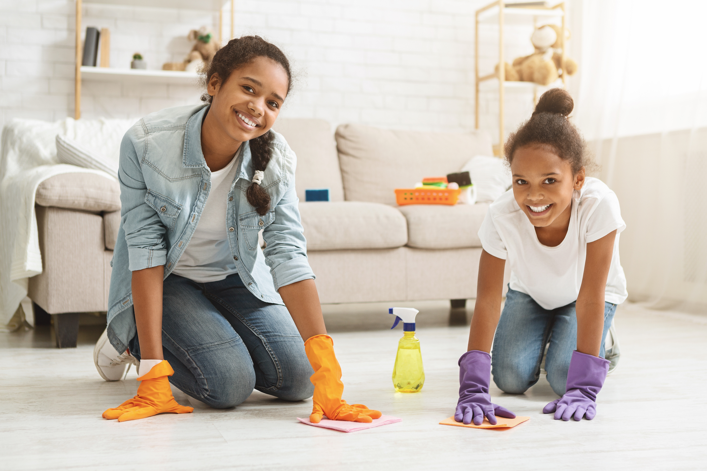 two adorable girls cleaning carpet at home KXUQA9F