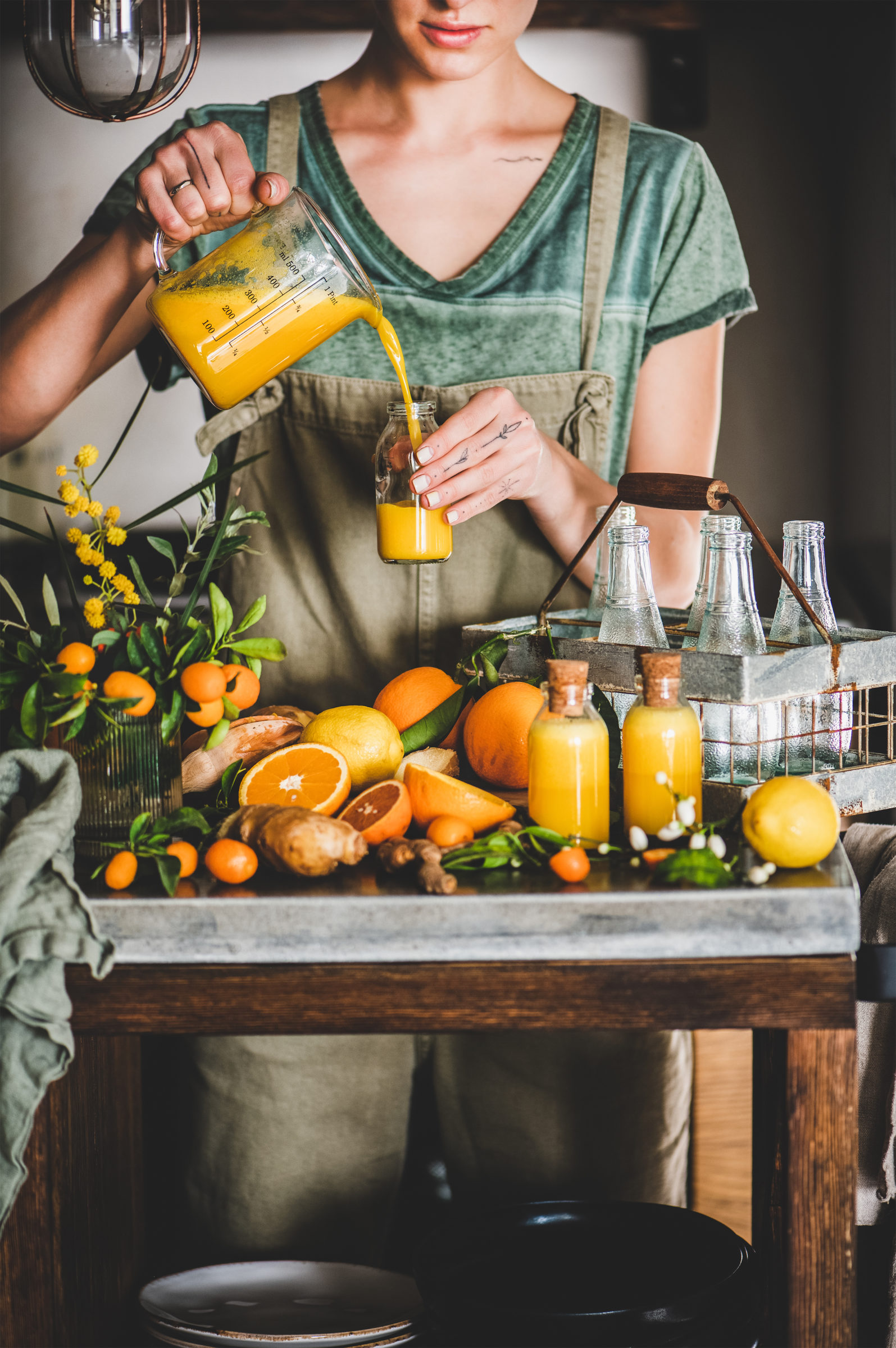 young woman pouring fruit immune boosting drink to VA4TZX2