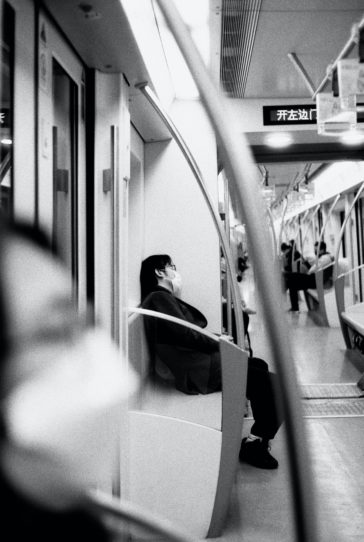 grayscale photo of woman in black jacket sitting on train