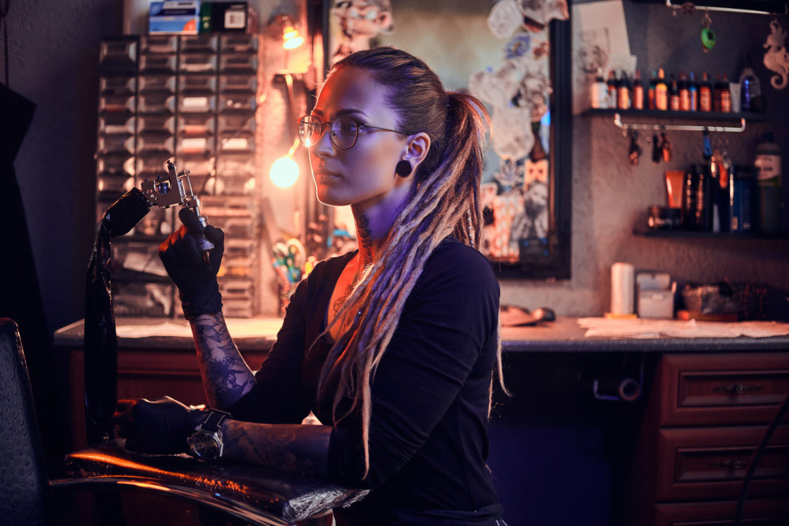 Young pretty tattoo master with dreadlocks and glasses is taking short break while holding tattoo machine.