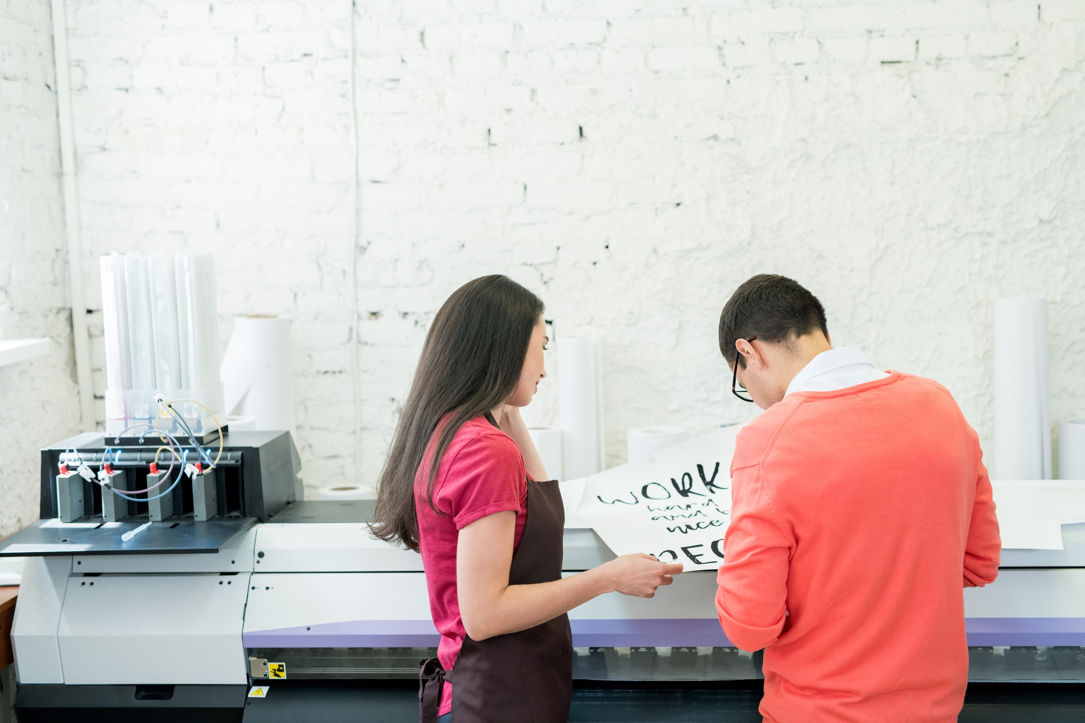 printing specialists examining banner in office E8YDC7K