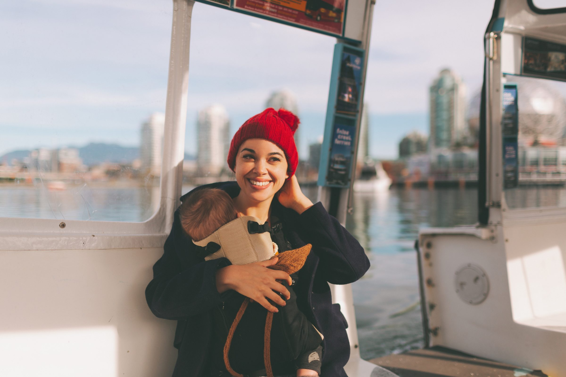 a woman wearing her baby in a carrier travelling i 5QE2BB2 1