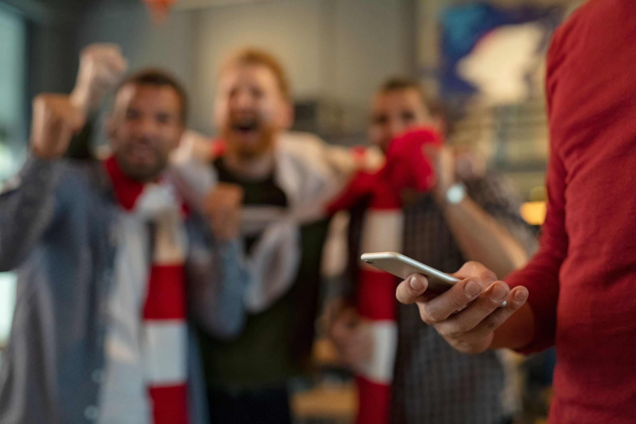 Close up of man holding smartphone and betting on the game while supporters celebrating the victory in background. Man using mobile in pub during football match. Soccer fans cheering for league in pub while man using smart phone to gamble with copy space.