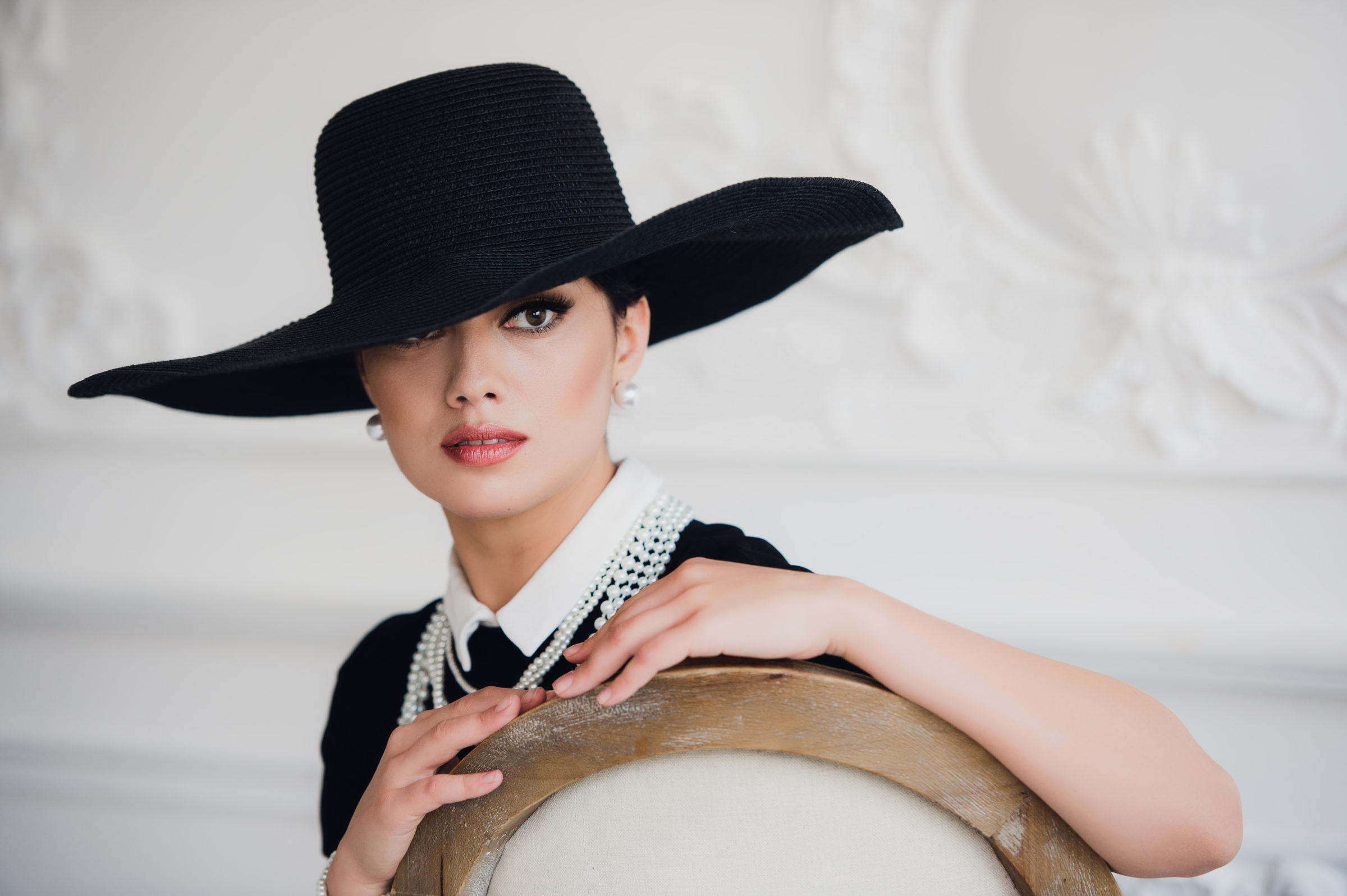 elegant woman in black dress with a hat sitting on PKSNGRY