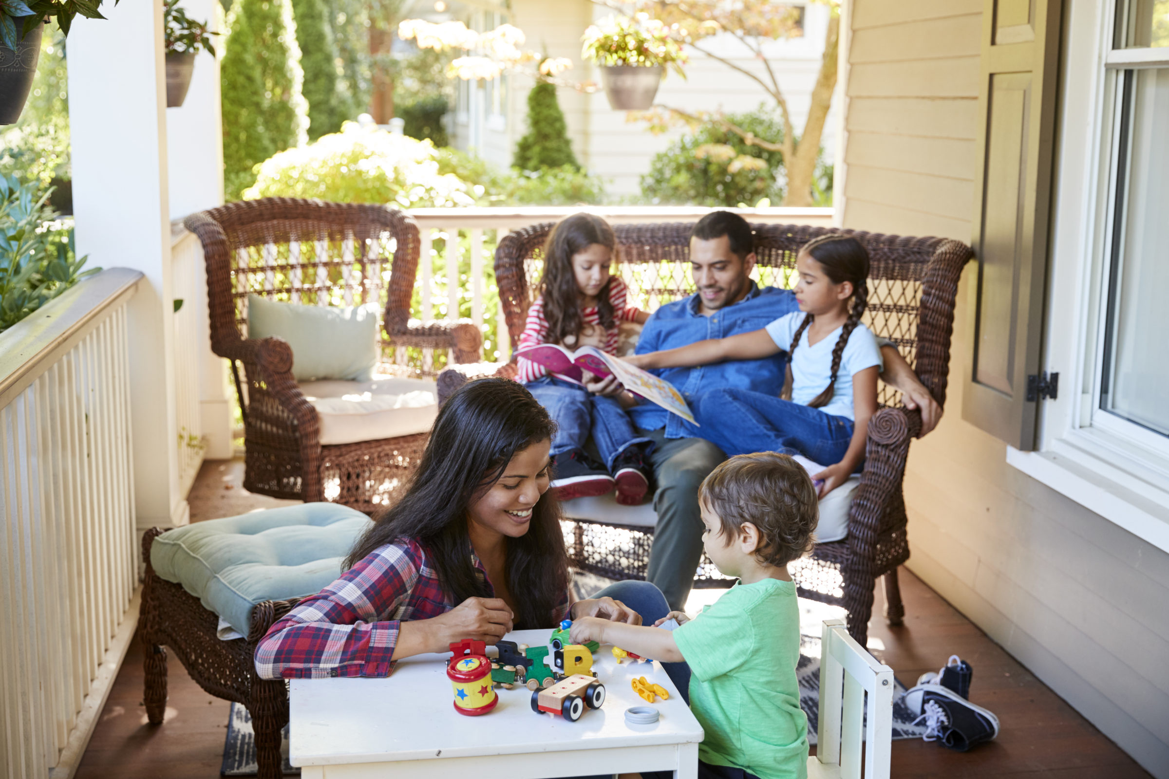 family sit on porch of house reading books and pla PFY8LZS