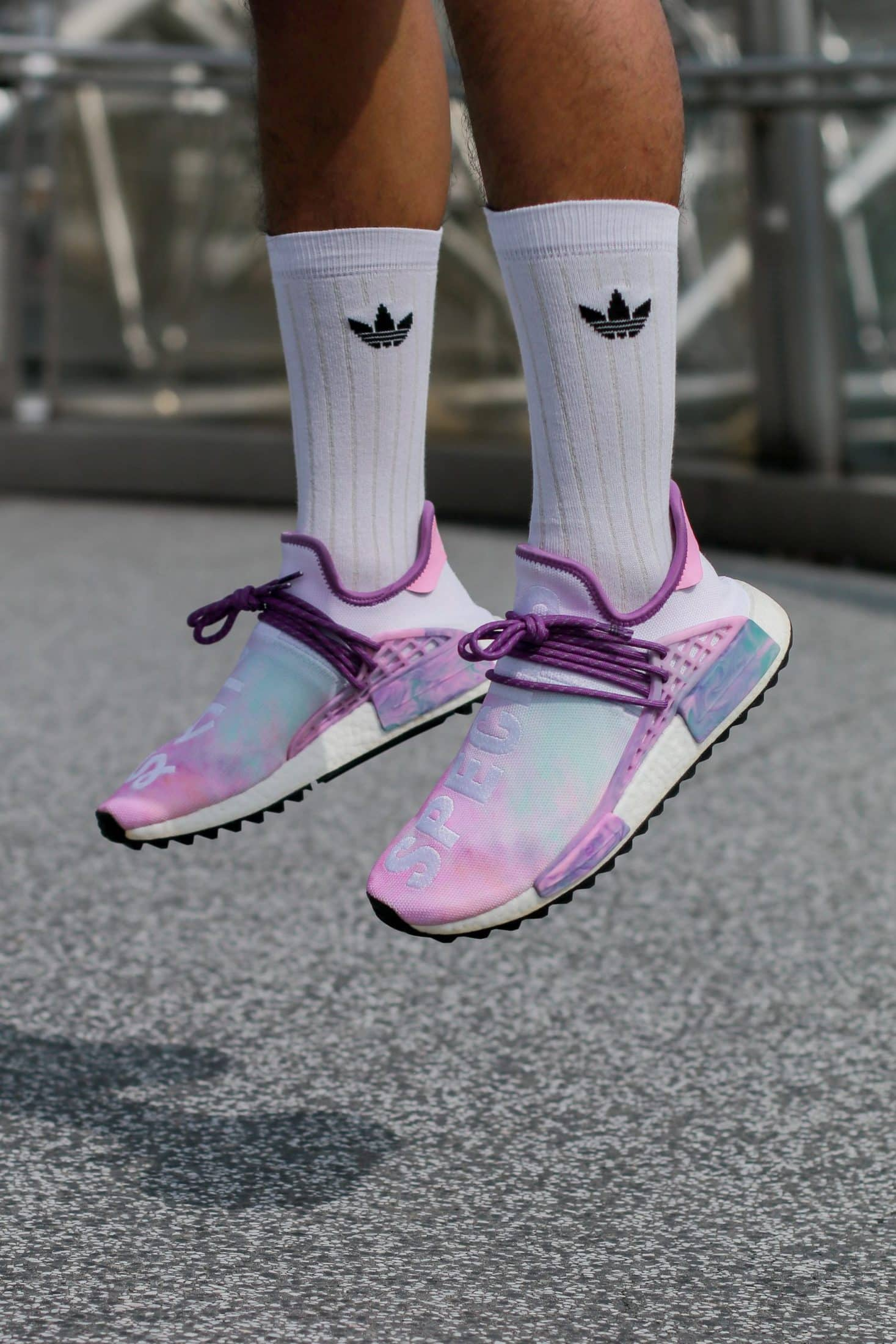 person in purple and white running shoes jumping on air