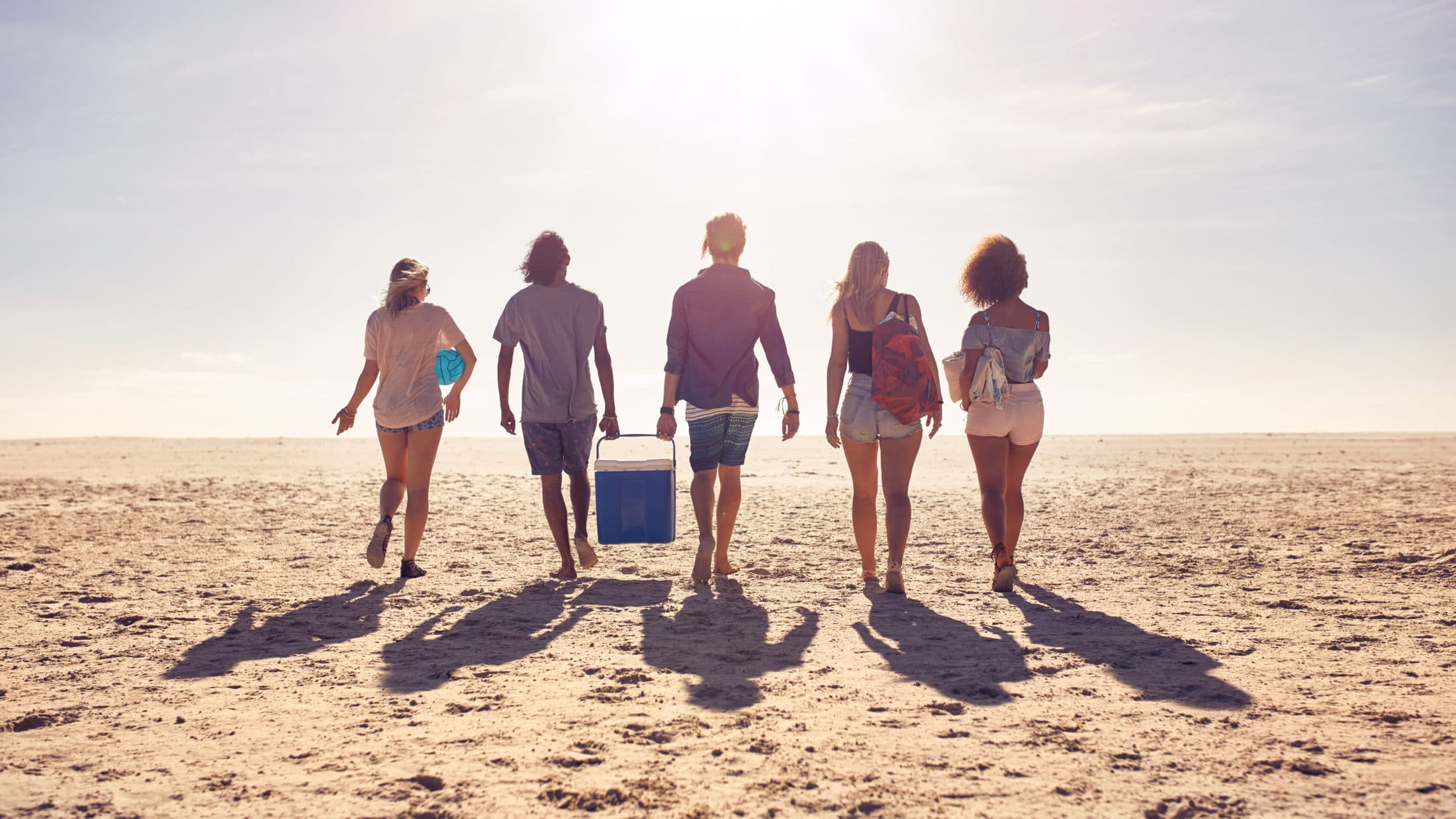 friends walking on the beach carrying a cooler box PCVR2Z5 scaled