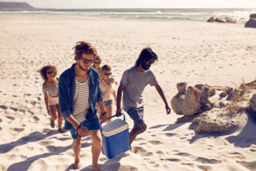group of friends carrying cooler to party on beach P6CGPJK