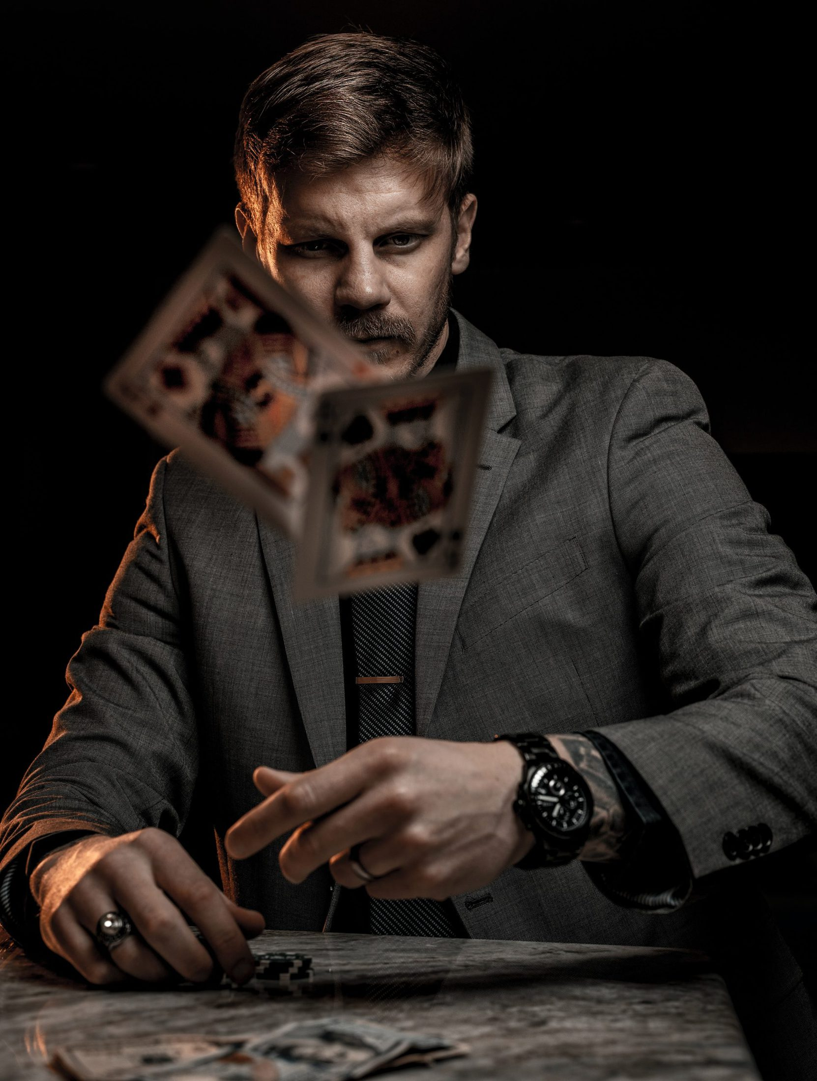 man in gray suit jacket holding jack of diamonds playing card
