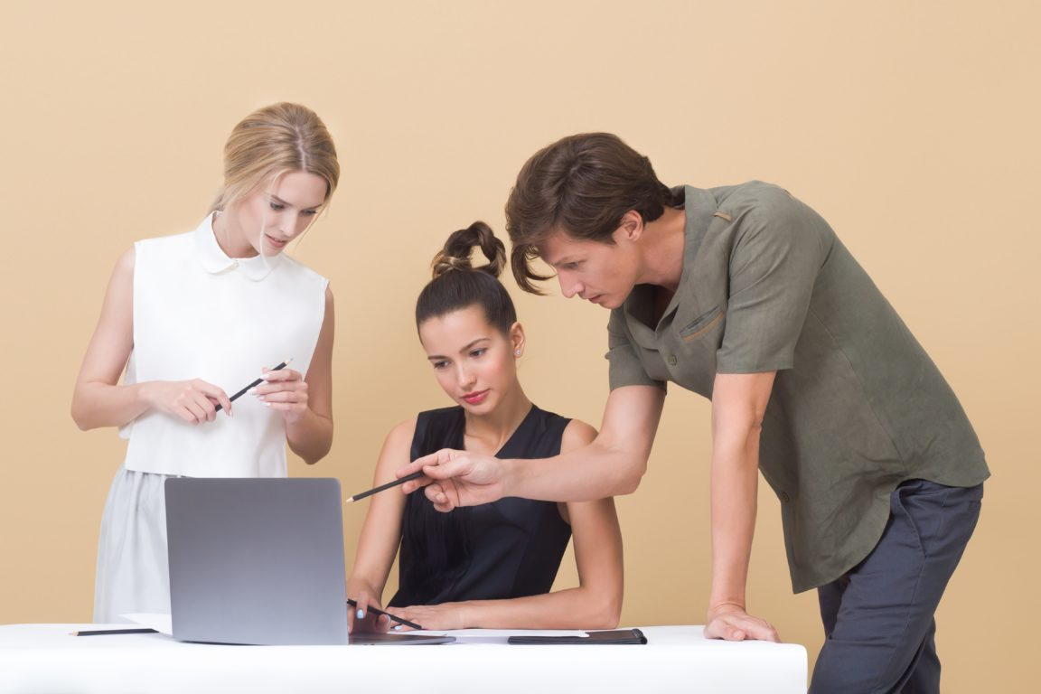 man teaching woman while pointing on gray laptop