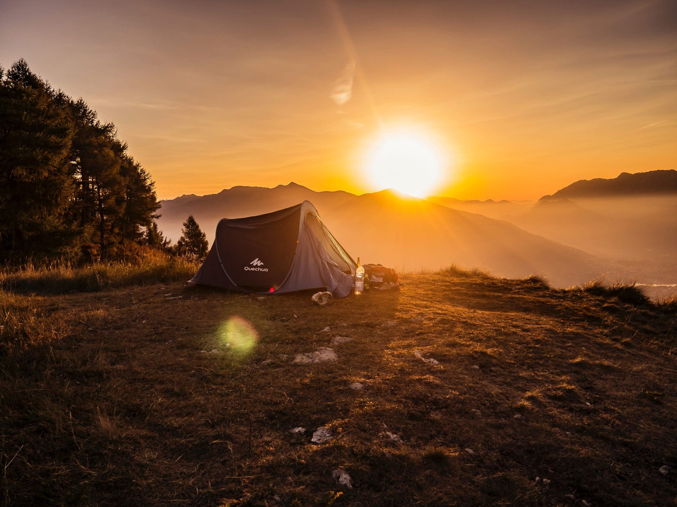 dome tent on mountain top with sun as background photo