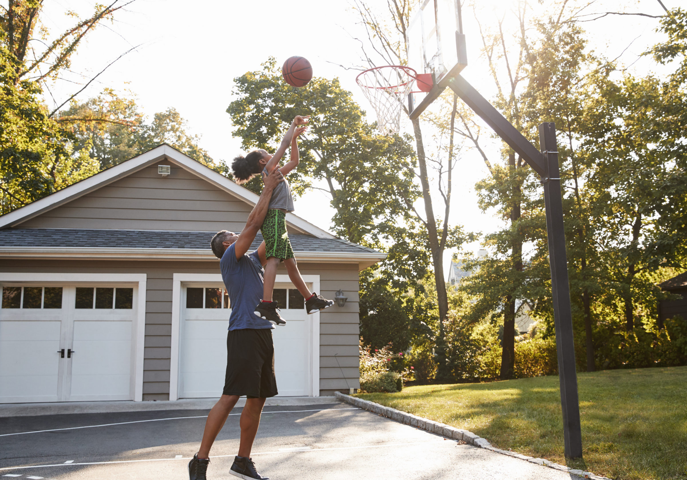 father and son playing basketball on driveway at h PYCK7GD